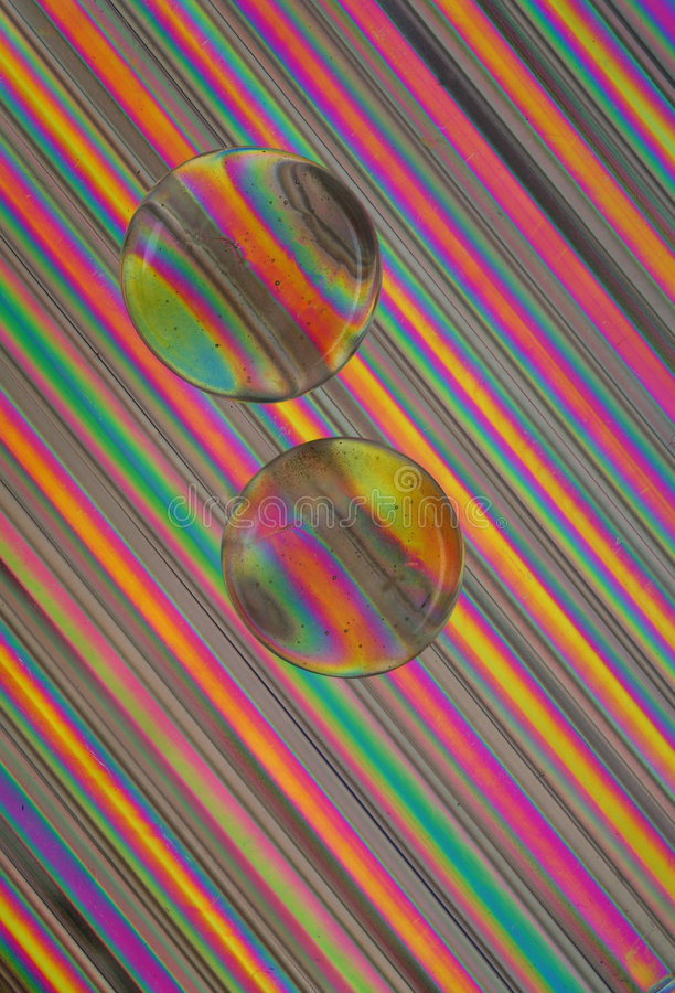 Glass Beads on Straws. Glass beads sit on a grouping of drinking straws in polarized light stock photo