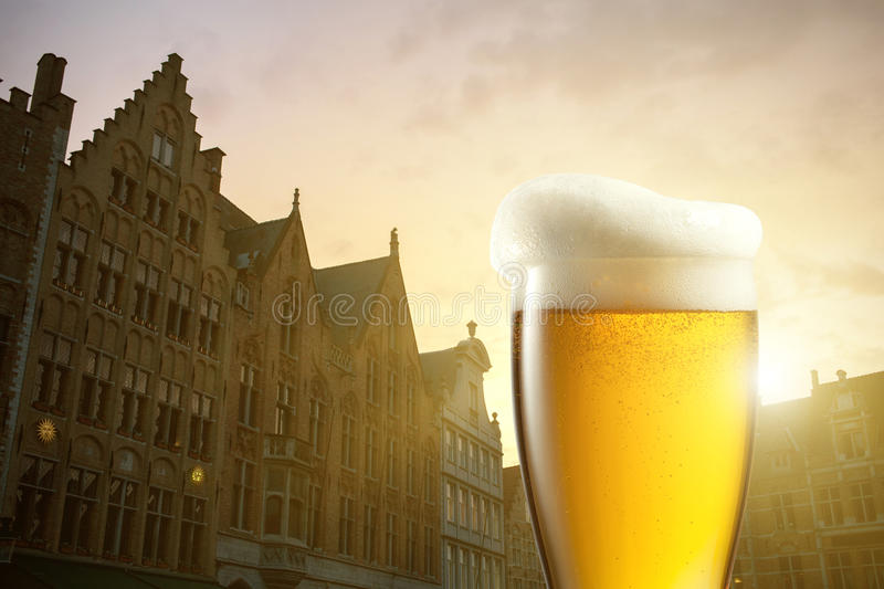 Glass of beer against silhouettes of houses in Bruges stock photo