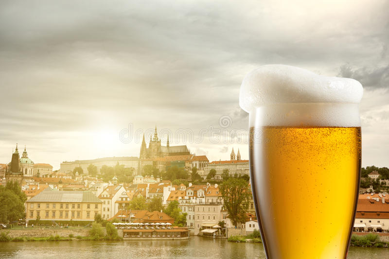 Glass of beer against view of the St. Vitus Cathedral in Prague stock image