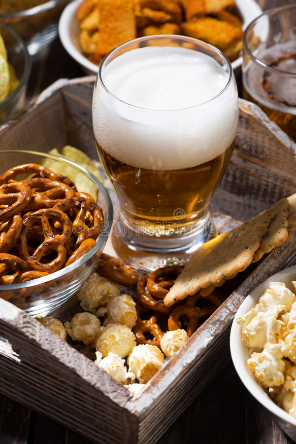 Glass of beer and an assortment of snacks, vertical stock photos