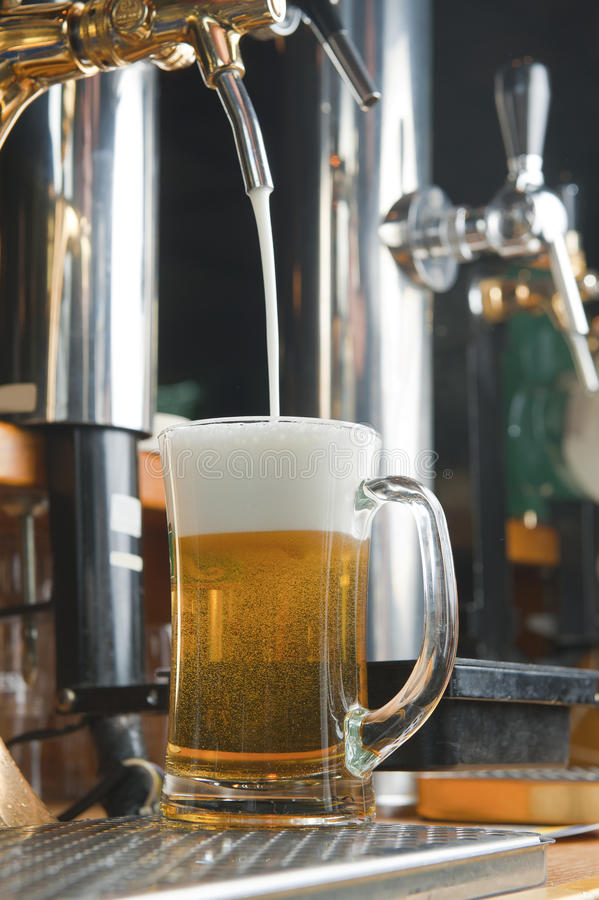 Glass of beer on the bar of bar. Beer gets into in glass. glass of beer on the bar of bar royalty free stock photos