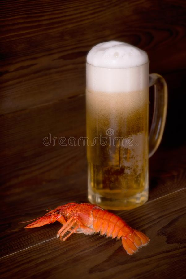 Glass with beer and a boiled crayfish on a wooden table. Glass with beer and a boiled crayfish lie on a wooden table royalty free stock photos