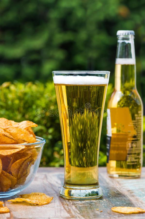A glass of beer and a bowl of crisps stock photos