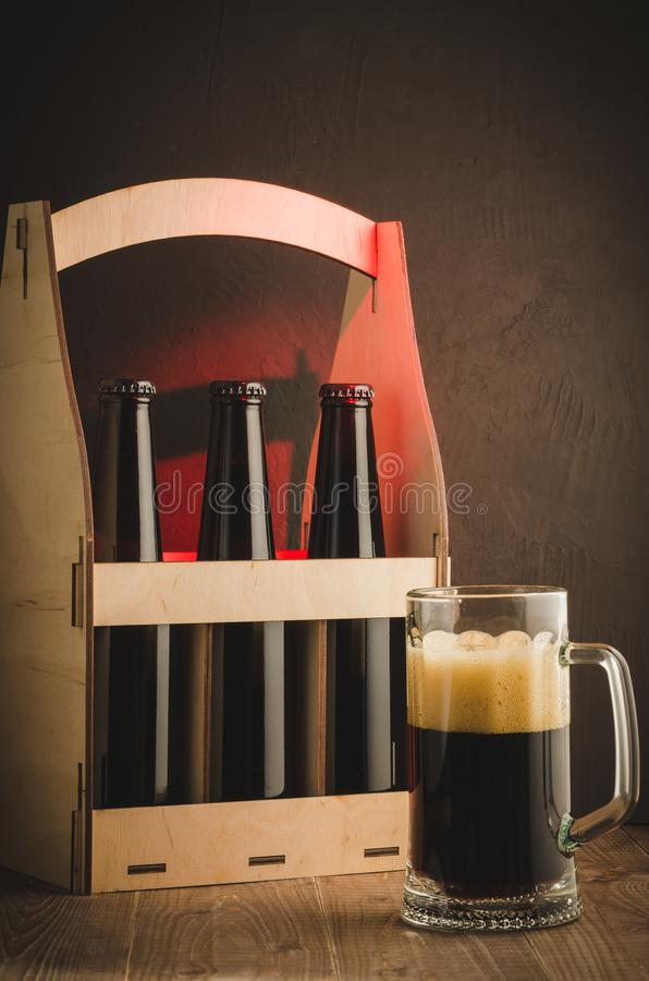 Glass of beer and box with bottles/glass of beer and box with bottles on a red light. Selective focus. Case wooden crate three dark party bar gourmet drink royalty free stock photos