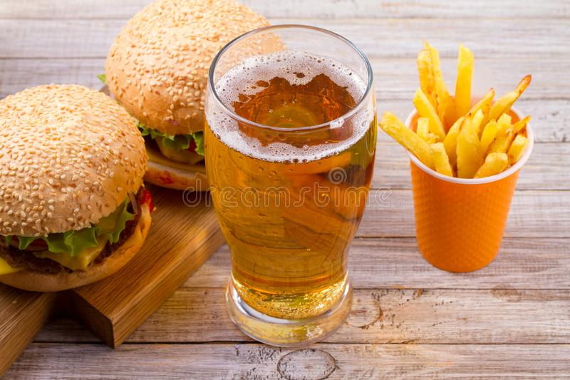 Glass of beer with burger and fries on wooden background. Beer and food concept. Ale and food. Glass of beer with burger and fries on wooden background. Beer stock photography