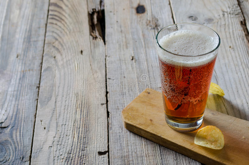 Glass of beer with chips on a wooden background stock photos