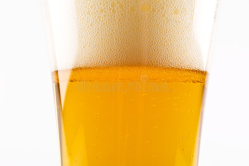 Glass of beer closeup. A closeup of a glass of beer showing the bubbles and details of the foam. Isolated on a white background royalty free stock image
