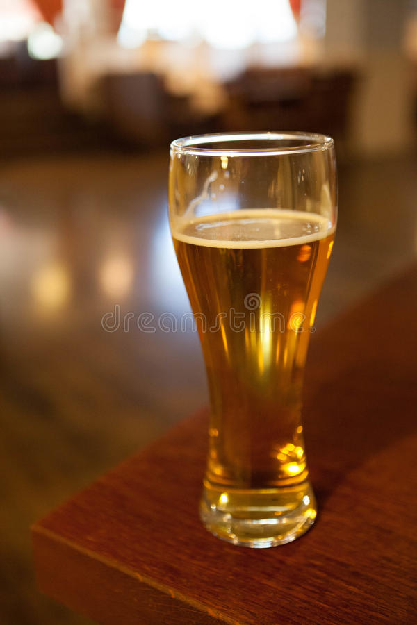 A glass of beer on the corner table in the restaurant stock photography