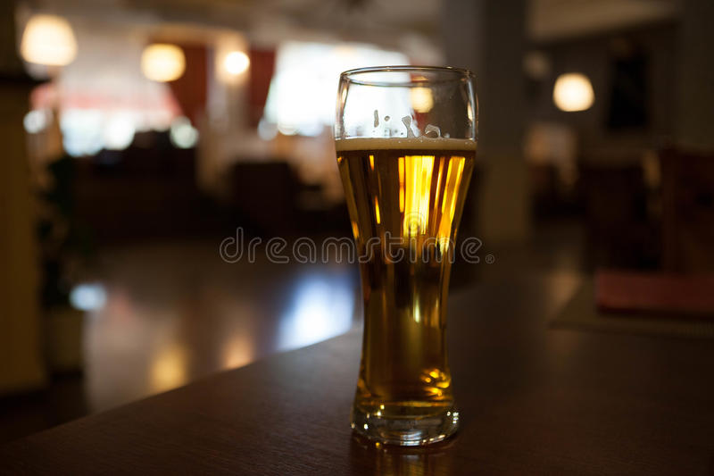 A glass of beer on the corner table in the restaurant.  stock image