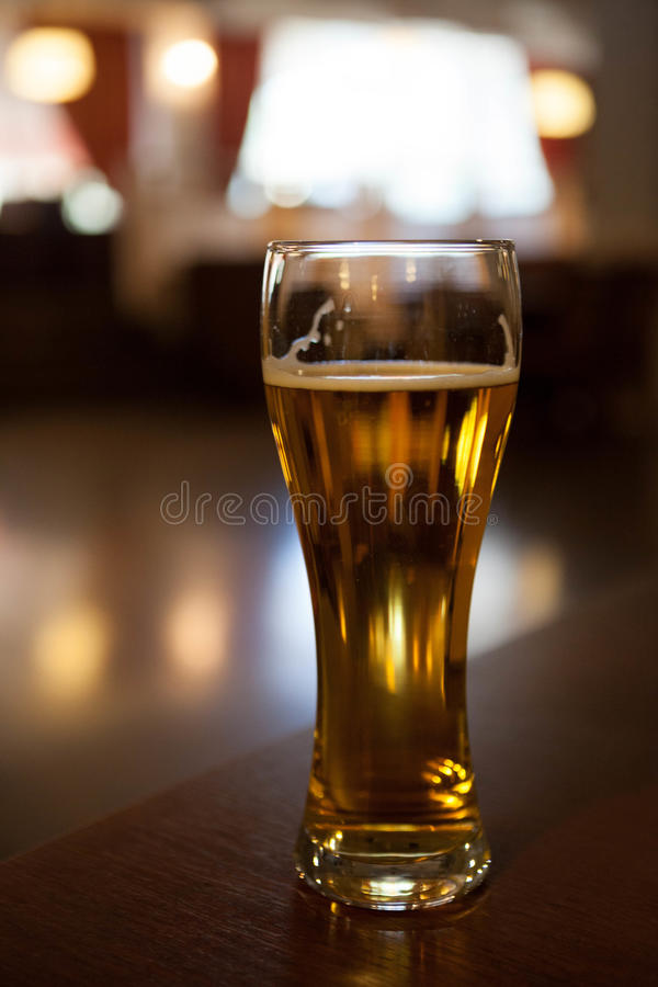 A glass of beer on the corner table in the restaurant.  stock photo