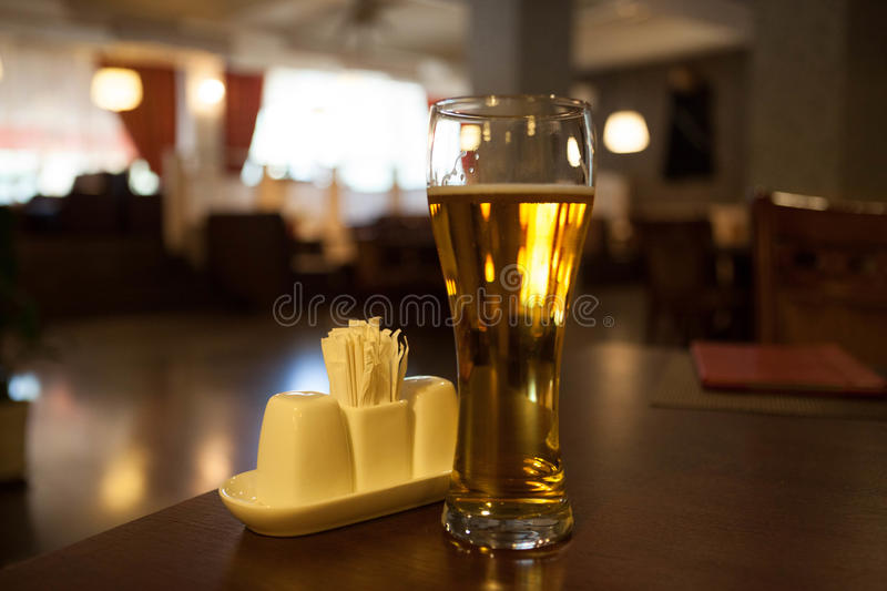 A glass of beer on the corner table in the restaurant stock image