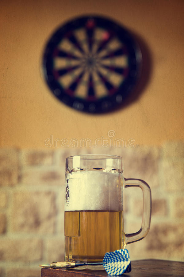Glass of beer and dartboard, filtered stock photo