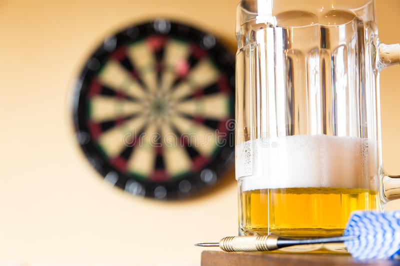 Glass of beer and dartboard. In a pub royalty free stock photo