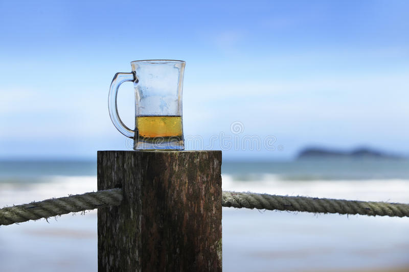 Glass of beer. Beer glass at the edge of a blue background stock images