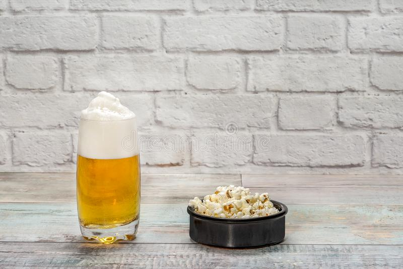 Glass of beer with foam and bowl with popcorn. On a white bricks background stock images