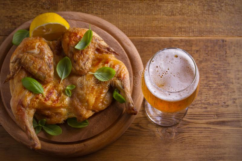 Glass of beer and grilled chicken. Well-baked and juicy chicken is good food to glass of ale. Beer and meat. royalty free stock images