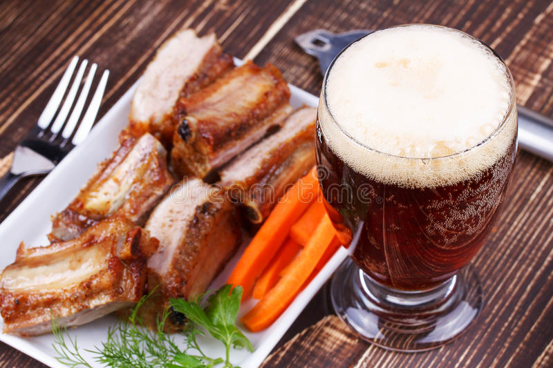 Glass of beer, grilled pork ribs and fresh carrot stock images
