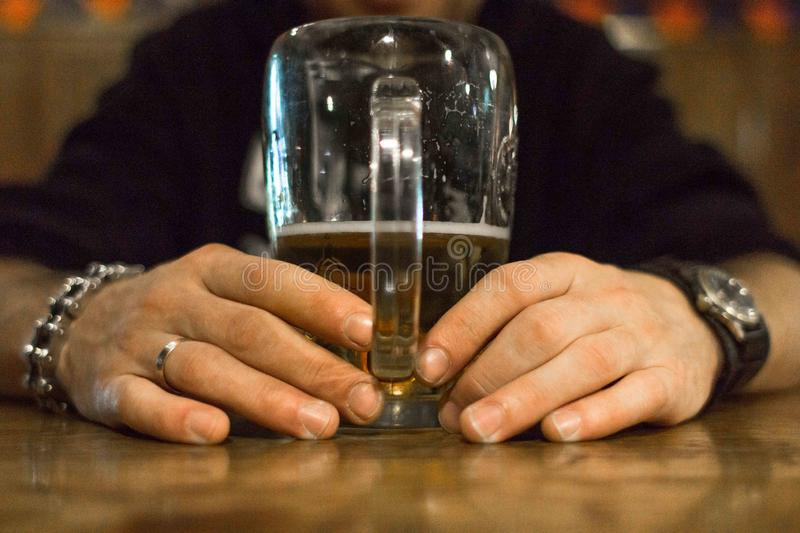 A man with a glass of beer at the bar. A glass of beer in hand. The man in the pub. Brewing culture. Drink on the bar. Bad habit. Alcoholic drink. Beer holiday royalty free stock photos