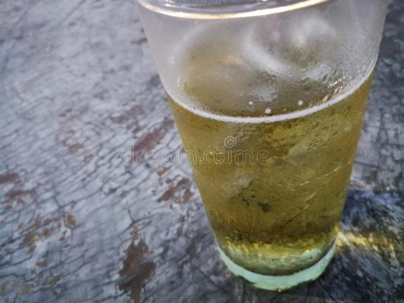 A glass of beer with ice on wood background stock photos
