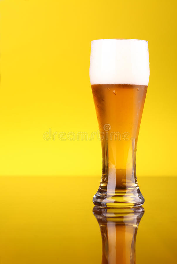 Glass of beer. Glass of light beer over a bright yellow background royalty free stock photo