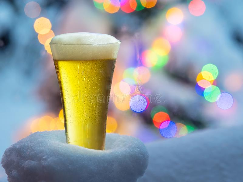 Glass of beer with magic Christmas lights at the background.  stock photography