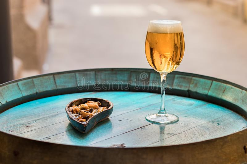 A glass with beer and mussels on a wooden wine barrel as a table. A drink glass with beer next to a plate with mussels without shell placed on a wooden barrel as stock photography