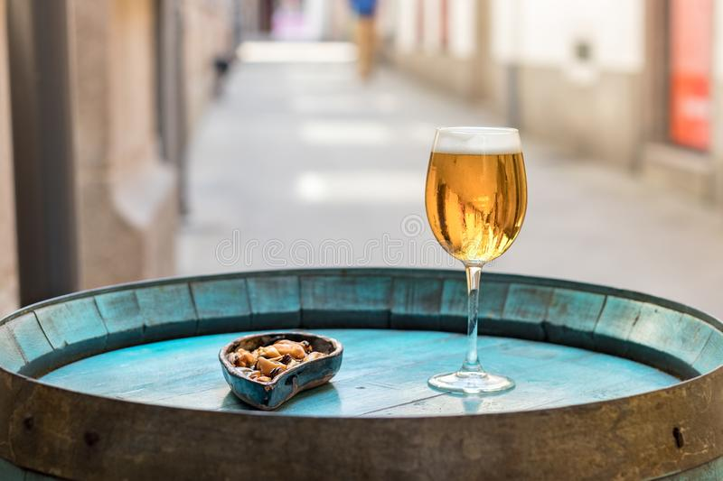 A glass with beer and mussels on a wooden wine barrel as a table. A drink glass with beer next to a plate with mussels without shell placed on a wooden barrel as stock images