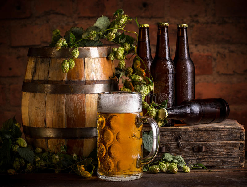 Glass of beer. Old oak barrel and hops on wooden table stock photo