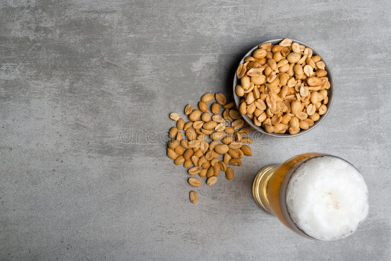 Glass of beer and peanuts stock images