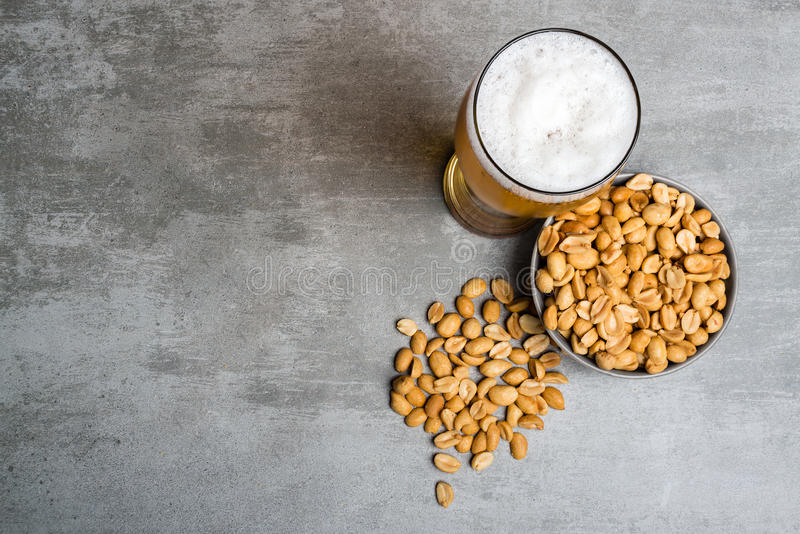 Glass of beer and peanuts royalty free stock image