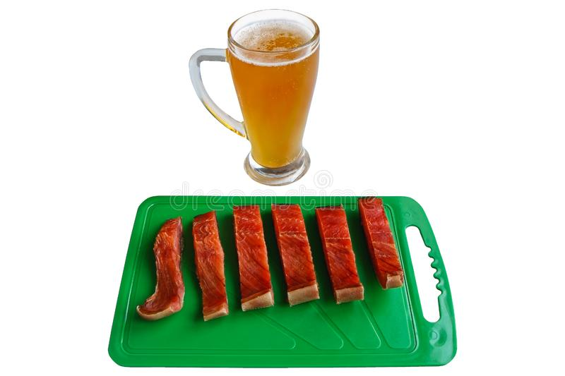 Glass of beer and pieces of red salmon fish on a green chopping board royalty free stock photography
