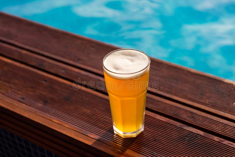 Glass of beer at the pool barside royalty free stock photo