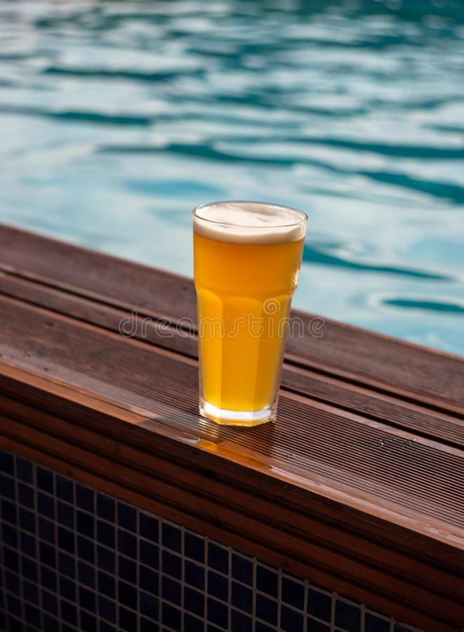 Glass of beer at the pool barside royalty free stock photography