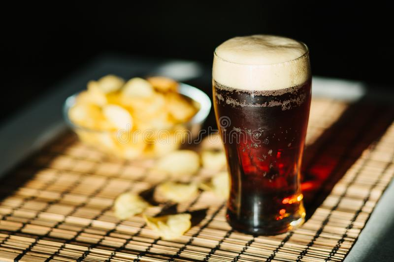 Glass of beer with potato chips stock photo