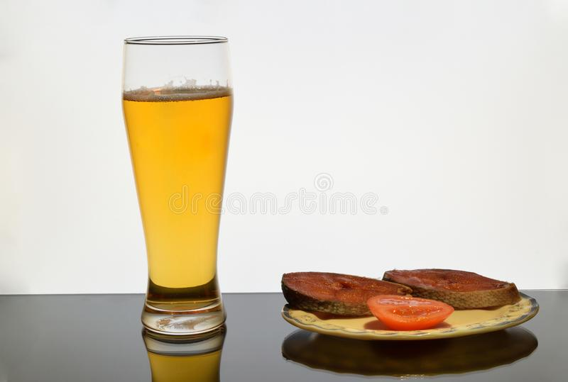 A glass of beer with a plate of salted fish and a tomato. stock images