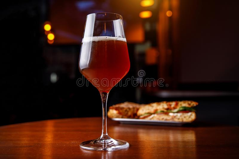 A glass of beer and a sandwich in a bar on a wooden table royalty free stock photo
