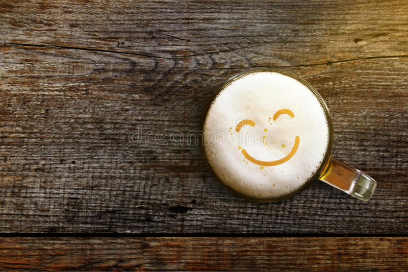 Glass of beer with Smiley face on Wooden table, Top view, Enjoy royalty free stock image