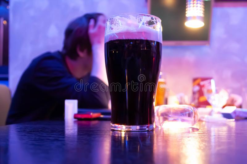 Glass with beer on the table in the bar. Against the background of a drunk man royalty free stock photos