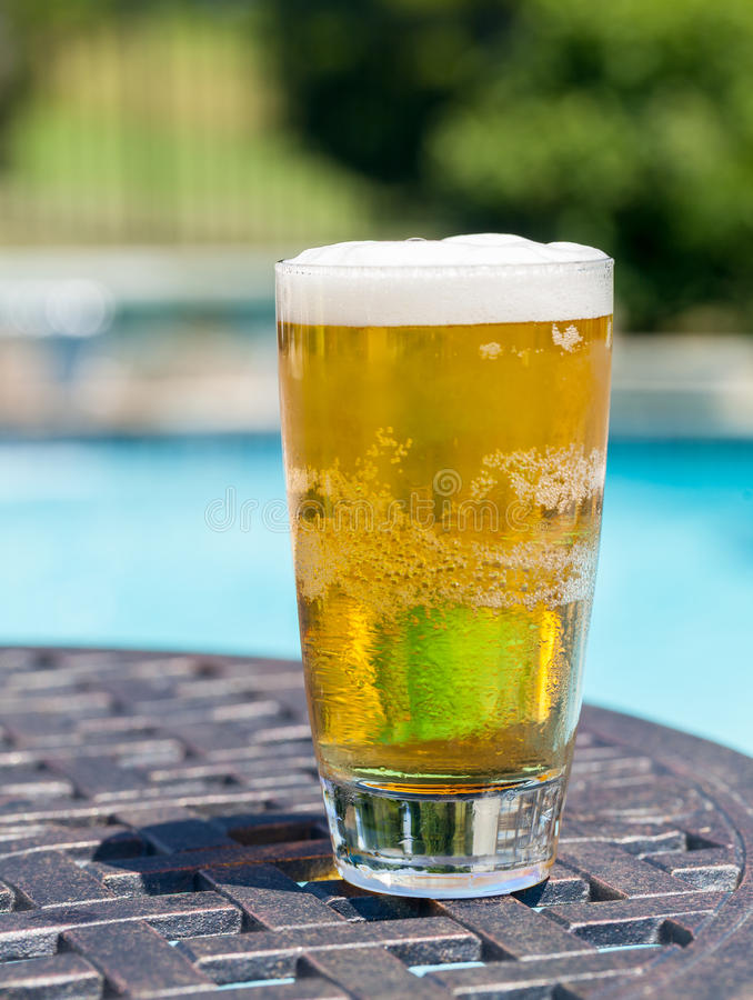 Glass of beer on table by poolside royalty free stock photography
