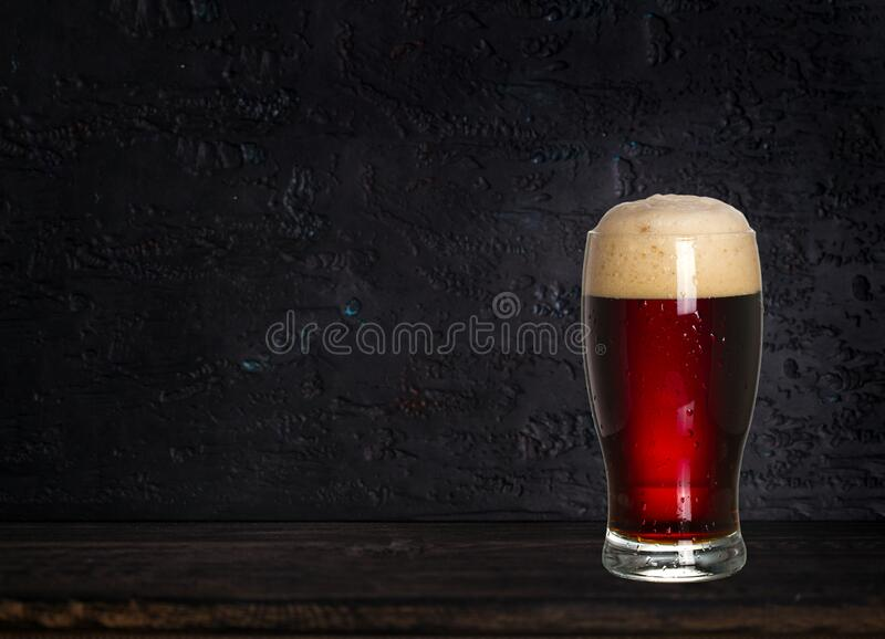Glass of beer on wood dark background with copyspace for text. royalty free stock images