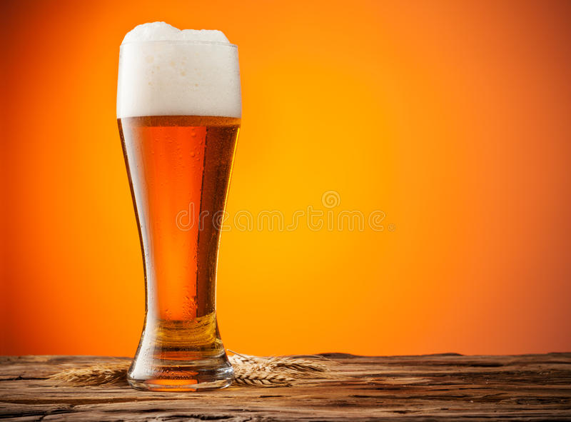 Glass of beer on wood with orange background royalty free stock photography