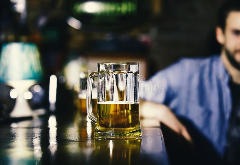 Glass of beer on wooden bar counter. Man sits behind glass of light beer. Alcohol beverage concept. Glass of draft beer on blurred bar background royalty free stock photography