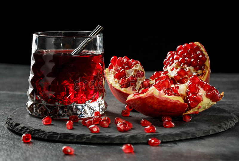 A glass of berry cocktail. Red garnet seeds. Fresh natural drink and a ripe pomegranate on a black background. Expensive stock photos