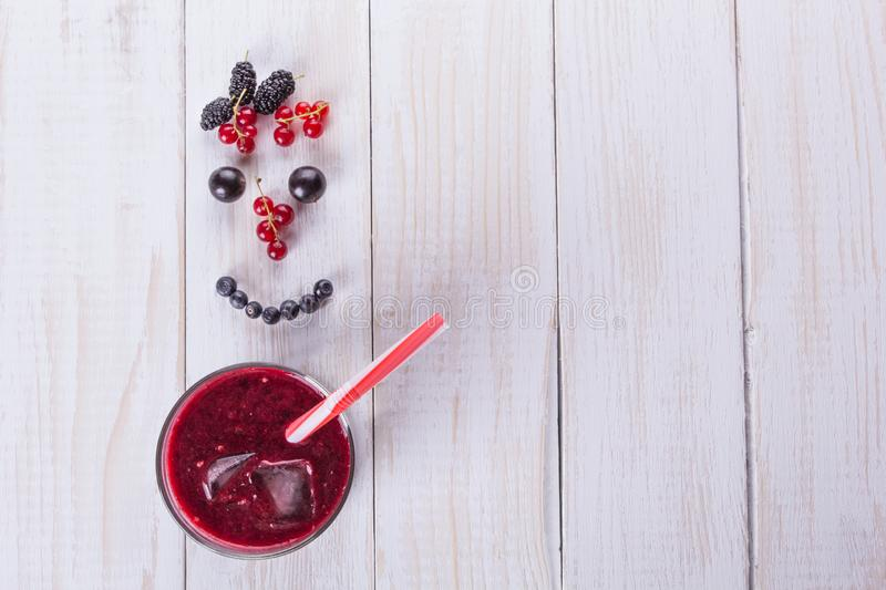 A glass of berry smoothie on white background. Smile from berries. Diet food concept royalty free stock photos