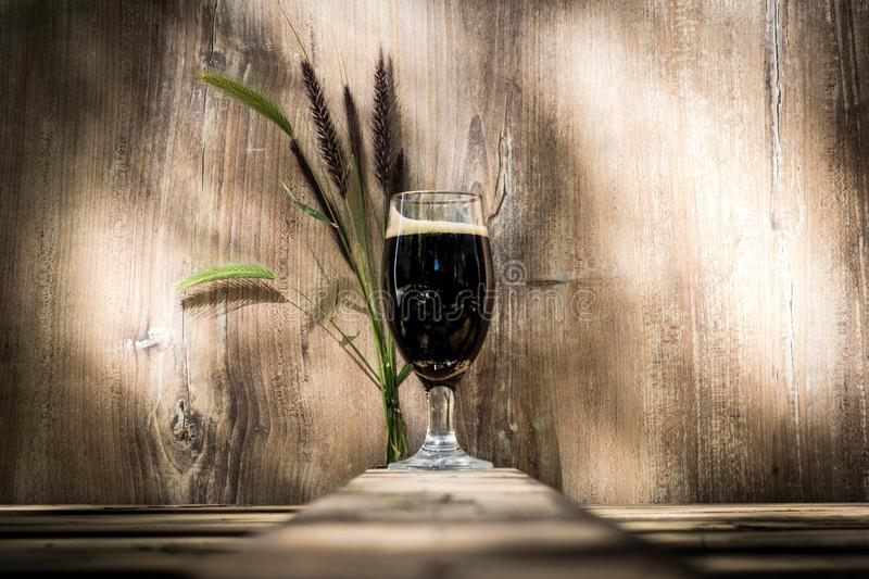Glass of black beer with foam. Wooden background royalty free stock photo