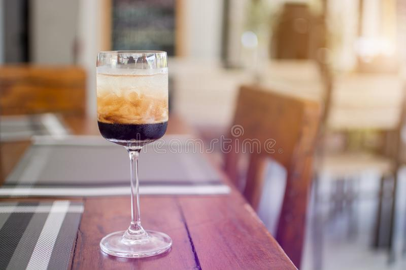 A glass of Black Russian alcoholic cocktail, liquor menu cool drink on the wooden table in the restaurant stock image