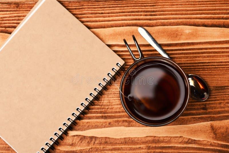 Glass of black tea with tea bag near tea spoon royalty free stock photography