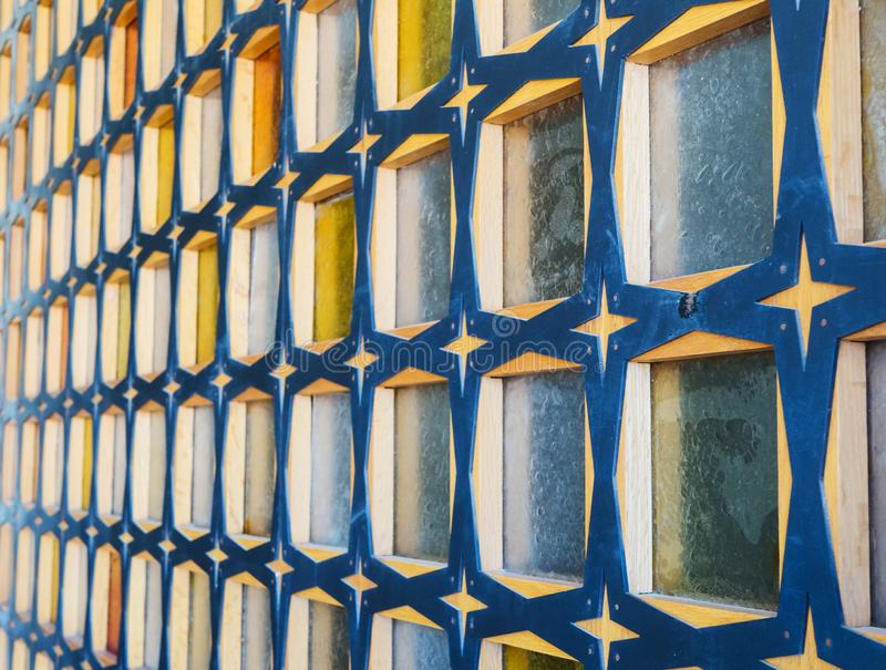 Glass block wall with wood of blue-yellow colors. Side view. Wall with pattern, texture. Glass block wall with wood of blue-yellow colors. Side view. Wall with royalty free stock photography