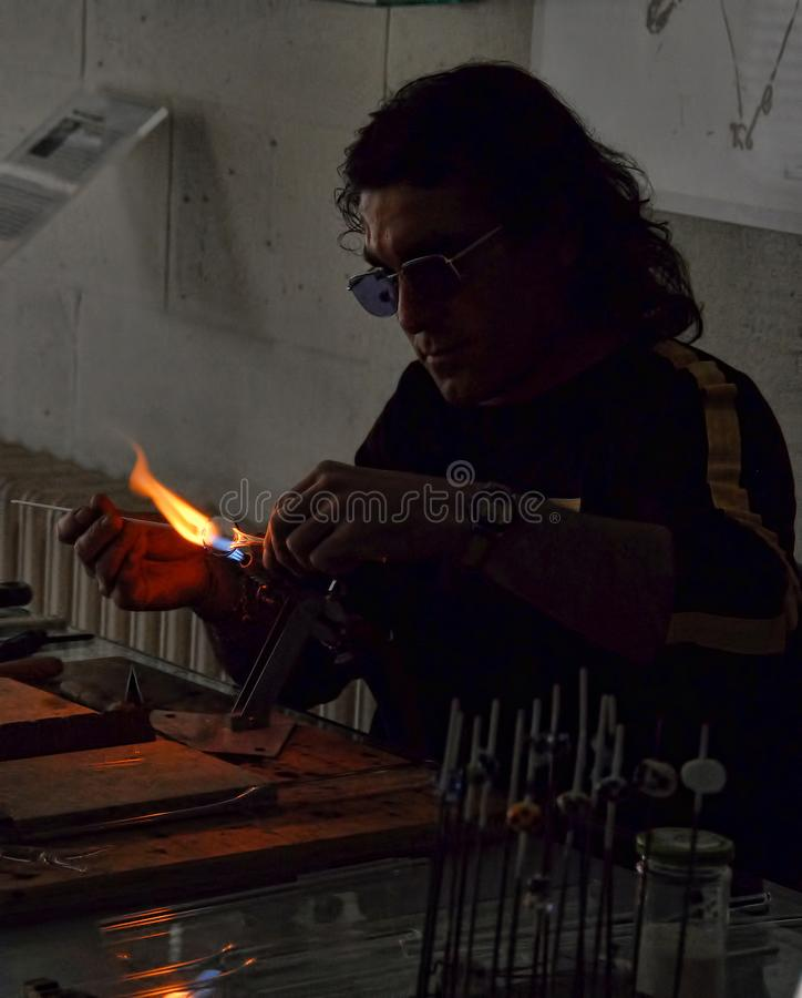 Glass blower heating a royalty free stock photography