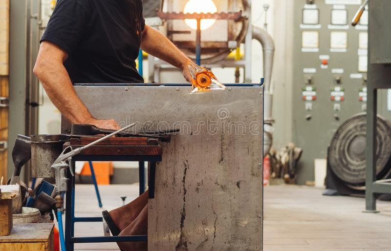 A Glass Blower Shaping Molten Glass into a Piece of Art. Makes a flower stock photo